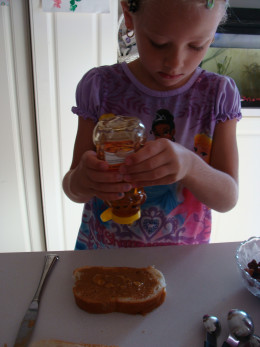 Grace adds the honey to the peanut butter.
