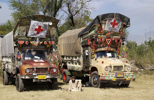 Happier days. A Pakistani rests between two supply trucks at a makeshift helicopter in Pakistan, Oct. 28, 2005. The Defense Department is delivering disaster relief to Pakistan, parts of India and Afghanistan following a devastating earthquake.