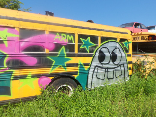 "Graffiti painted on a bus at the ""school bus graveyard."""