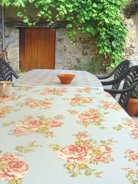 Don't these two table cloths liven up this outside dining space? A shady arbour near Videix in S W France complete with grape vines and an old barn door.