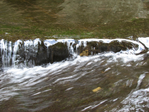 Water cascading over a low edge and change direction and speed rapidly.