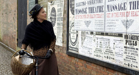 Spitfire Charlotte looking at posters advertising her father's miracle cure for female hysteria.