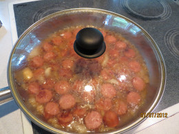 Kielbasa dish cooking with cover