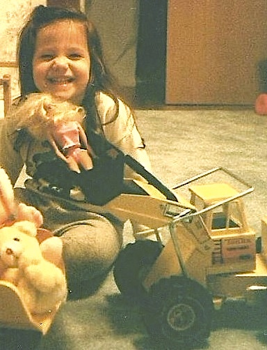 My daughter playing with her Tonka dump truck full of stuffed toys on the left,  and giving Barbie a ride in the bucket of her front end loader.  I preferred these kinds of toys as a child and daughter did too, except for books being her #1 favorite.
