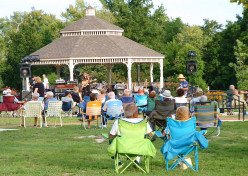 Residents and visitors enjoying a free summer concert at the park.
