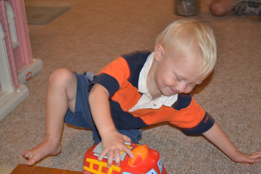 Son playing with red truck