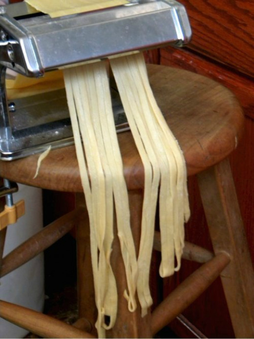 Here, fresh pasta dough is rolled through a roller to create fettuccine