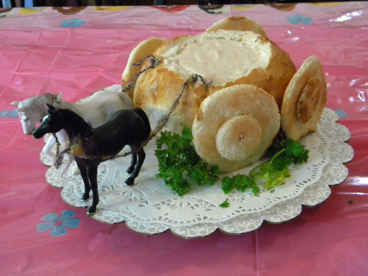 A round loaf of bread, hollowed out and filled with dip becomes Cinderella's Coach.