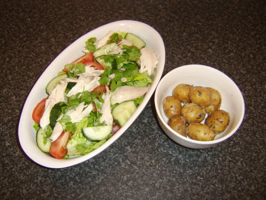 Cold chicken salad and minted new potatoes is ready to serve