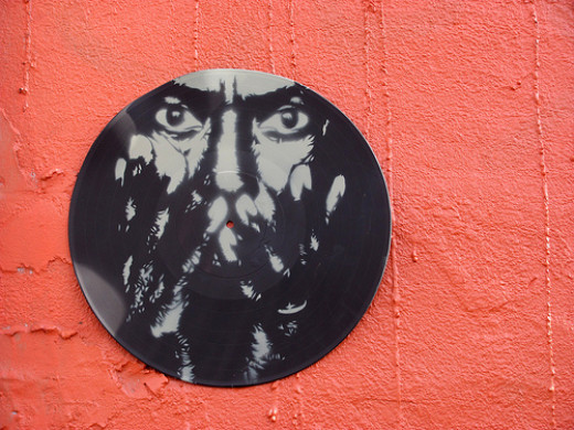 Miles Davis, stenciled on a vinyl record then glued to the side of a building.
