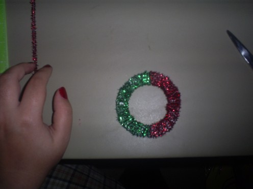Make a cute Christmas wreath decoration made with cardstock and sparkly pipe cleaners.