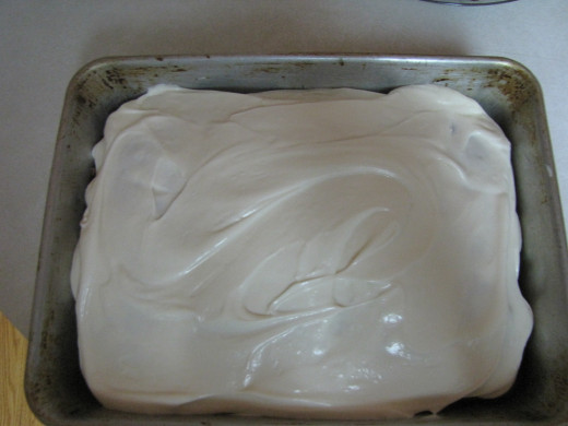 Spread cream cheese frosting on top of flat cake to cover the holes.