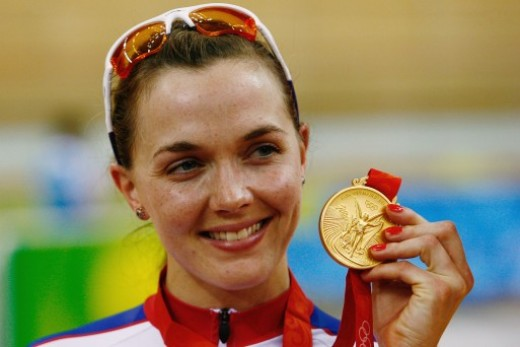 The champion cyclist shows off her gold medal from the women's sprint at Beijing