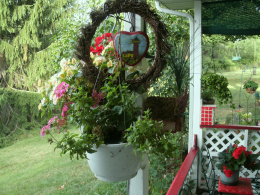 This is a photo of the patio I built, the wreath I made, the hanging baskets I planted and finally the wood burning and painted heart shaped plaque I crafted.
