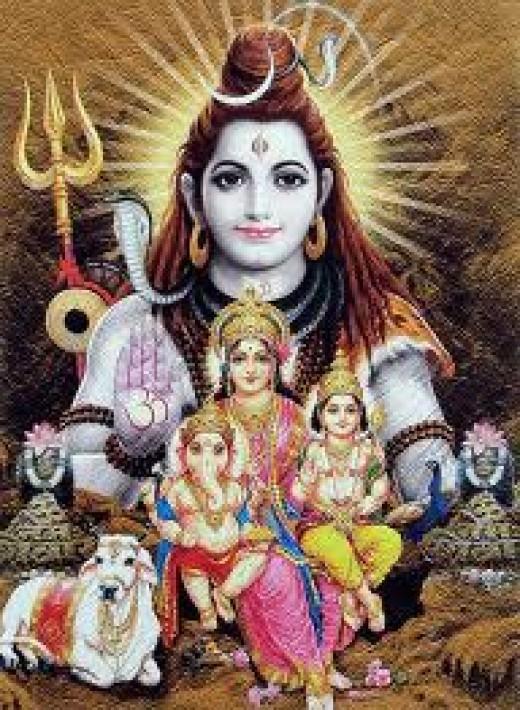 God Shiva with his wife Goddess Parvati and his two sons, God Ganesha and God Karthik. See God Ganesha holding a plate of sweet dumplings.