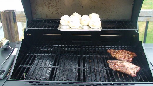 Stuffed mushrooms sitting in a small cup muffin tray on the top rack of the barbecue cooking along with some juicy steak!