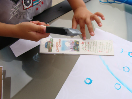 Alex carefully glues the cardboard to add his decorative paper.