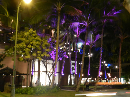 Waikiki lights up at night as tourists walk up and down the strip, dining, sightseeing, shopping, and drinking.