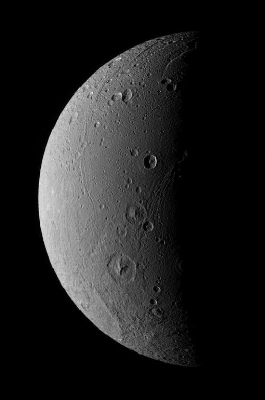 This view of the leading hemisphere of Dione clearly shows up a huge number of impact craters - some of them enormous. You can also see scars characteristic of ancient geologic activity.