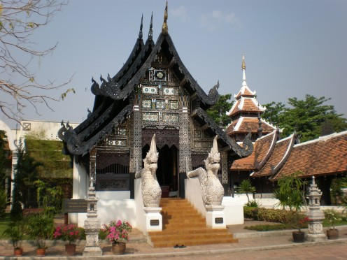 Beautiful chapels within the Buddhist temple and compound of Wat Chedi Luang. Notice the lovely facade embellishment, carved gable, wooden roof and guarding nagas. Chang Mai, Thailand.