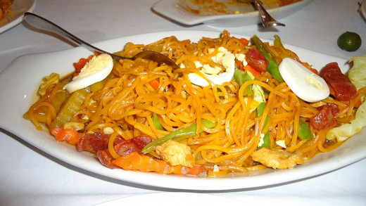 Filipino Pancit (noodles) topped with hardboiled eggs, shrimp, and chorizo.