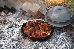 A cast iron Dutch oven, cooking a delicious meal.