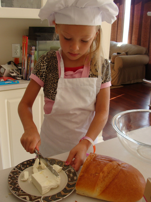 Grace carefully cuts the cream cheese into pieces.