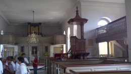 """A picture inside Bruton Parish of the pulpit.  Notice the """"sounding board"""" on top to project volume and the elevated position of the pulpit also."""