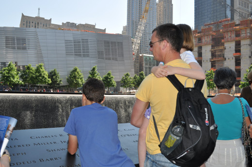 Taking in the 9/11 memorial in New York City - The Freedom Tower can be seen under construction on the right