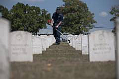 Petty Officer 2nd Class William S. Herbst, yeoman, assigned to the embarked staff aboard the U.S. 7th Fleet command ship USS Blue Ridge, weeds grave stones at Clark Cemetery during a community service project.
