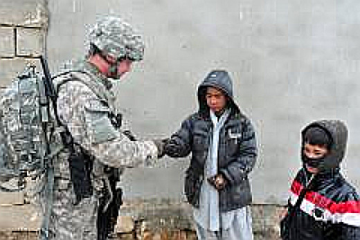 U.S. Navy Lt. j.g. Shane Coss, Ghazni Provincial Reconstruction Team information officer, hands out calling cards for the Guardian of Peace program to children during a village assessment in Touheed Abad Village in Ghazni province Feb. 6.