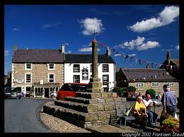 The top end of the market square, Middleham - the town is built on a gradient that rises toward the Coverdale road past here. Turn right to descend towards Leyburn