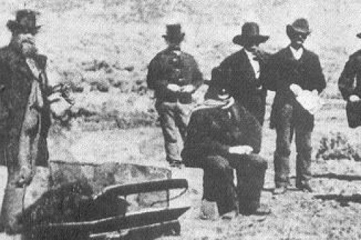 1875 photo of John D. Lee sitting next to his own coffin as preparation is made for his execution by firing squad.