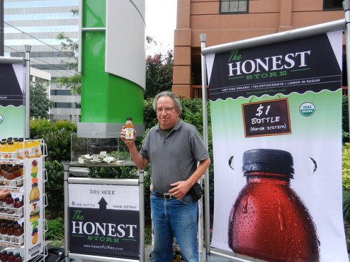 "he could have had a cold drink for free from the ""honor stand,"" in background, but chose to spend $1.00 to buy the same drink from the machine to the right."