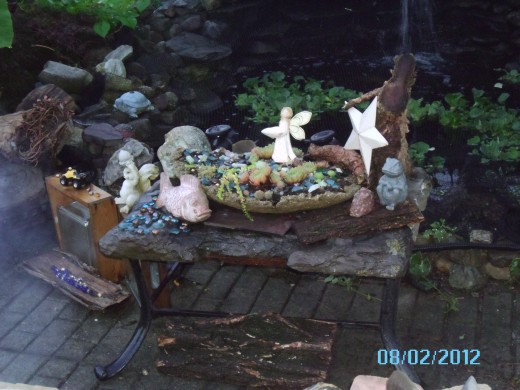 This table is made from an my old firepit frame and a piece of slate someone gave to me.On the edge sits the little frog on a piece of bark.