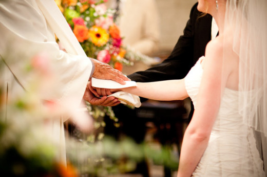 As the maid of honor, it's your job to hold the bride's bouquet while the couple exchanges vows