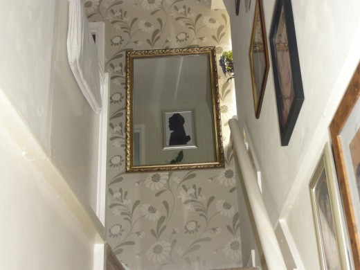 From the bottom of the stairs you can view the silhouette of my mother in the mirror on the wall.