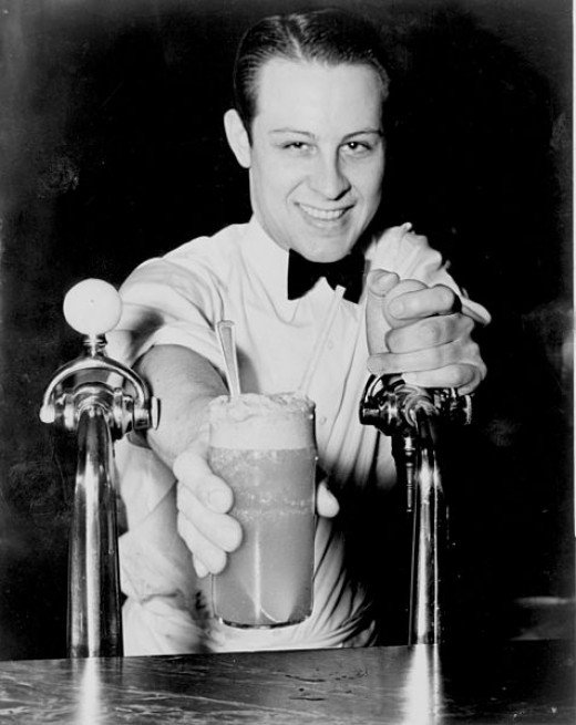 Soda Jerk passing ice cream and soda between two fountains 1936.