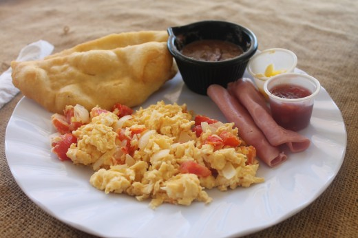 Belizean breakfast. Ham, scrambled eggs, beans and fry jacks with butter and jam on the side.