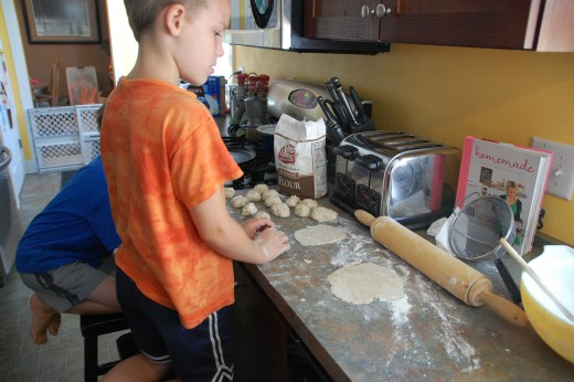 D splitting the dough and rolling out tortillas