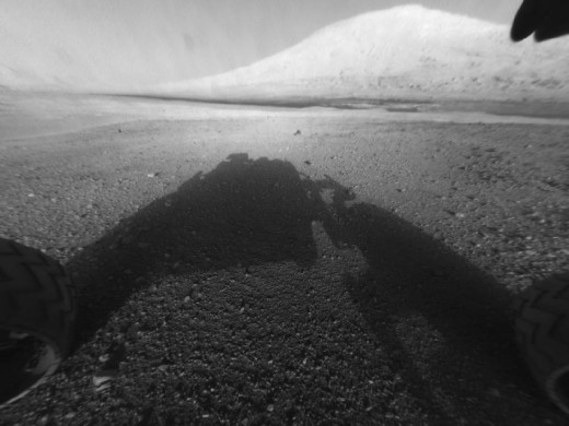 "Snapped by Curiosity after landing, sent back to Earth via Odyssey relay on August 6th. Mount Sharp is 3 miles tall. And yes, that's the rover's shadow. Its ""head"" is still tucked in; it will be several days before HD color camera is raised."