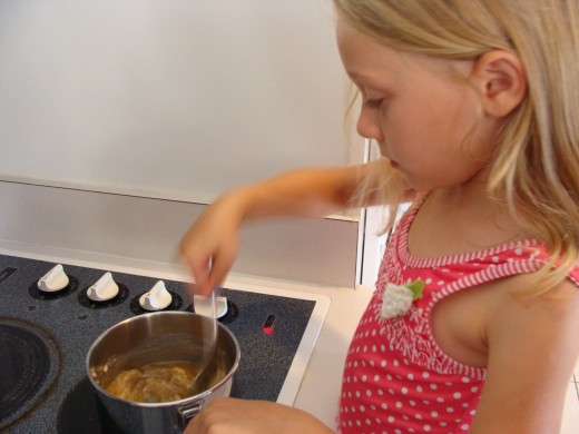 With parental supervision, children can comfortably get to know the proper way to use a stove.  Grace very carefully stirs the butter and sugar until melted.