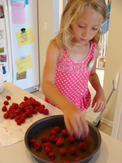 Grace adds the raspberries.