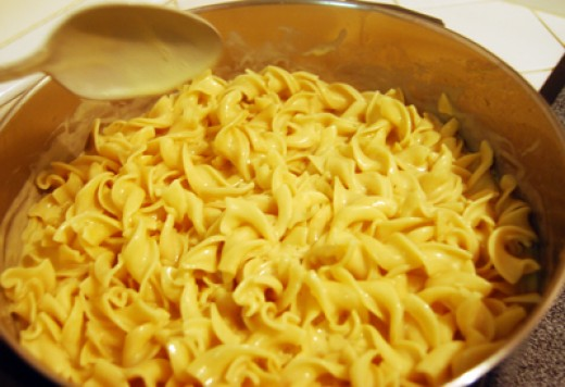 Mixing honey mustard sauce into finished noodles.
