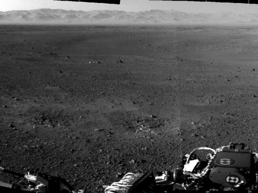 Pan across to rim of Gale Crater. There's two scars in the middle ground where the sky crane's retrorockets blasted away the dust to reveal bedrock.