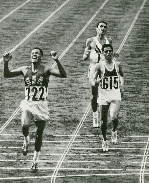 Billy Mills Crossing the Finish Line and Winning the GoldBilly Mills (Oglala Lakota), far left, crosses the finish line in first place during the 10,000 meters at the 1964 Olympic Games in Tokyo. (Photo courtesy of Billy Mills)