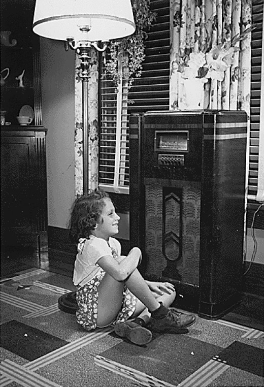 An American girl listens to a radio during the Great Depression.