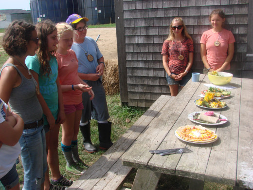 Kids present their dish as teachers look on.