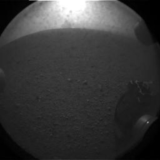 "The ""pyramid"" shape seen in the first hazcam shots behind Curiosity is the last of the dust cloud kicked up by the sky crane's crash. (It hit 20 seconds before this photo, taken 40 seconds after touchdown.) JPL planned this photo hoping to spot it."