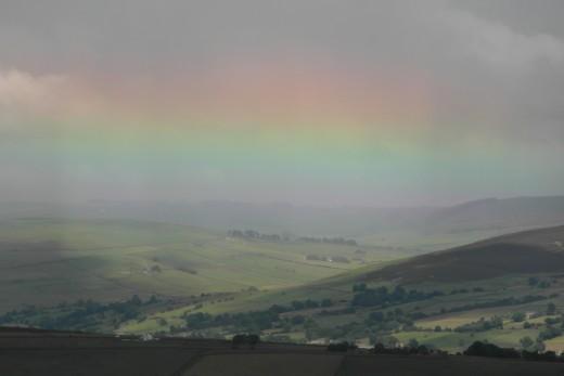 Shallow rainbow produced by high sun
